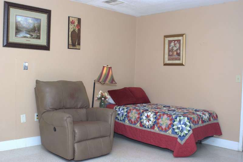 Hospice room with bed and comfy recliner chair.