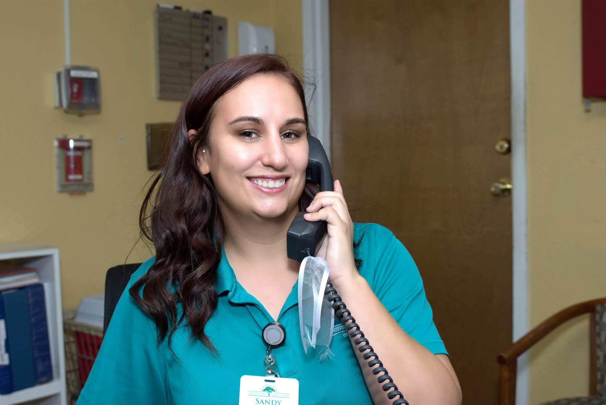 Staff member smiling with phone