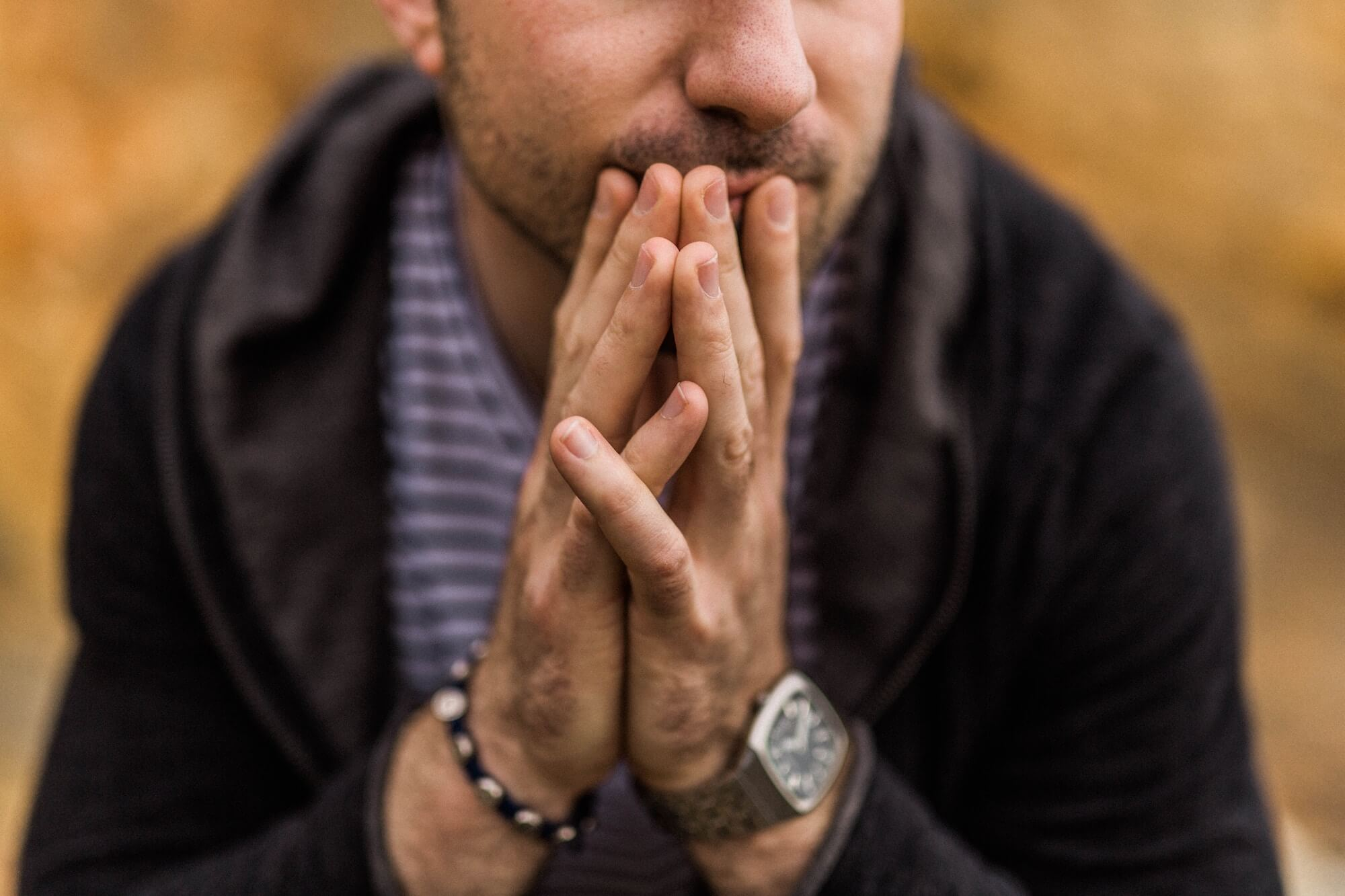 Man holding hands together in thought