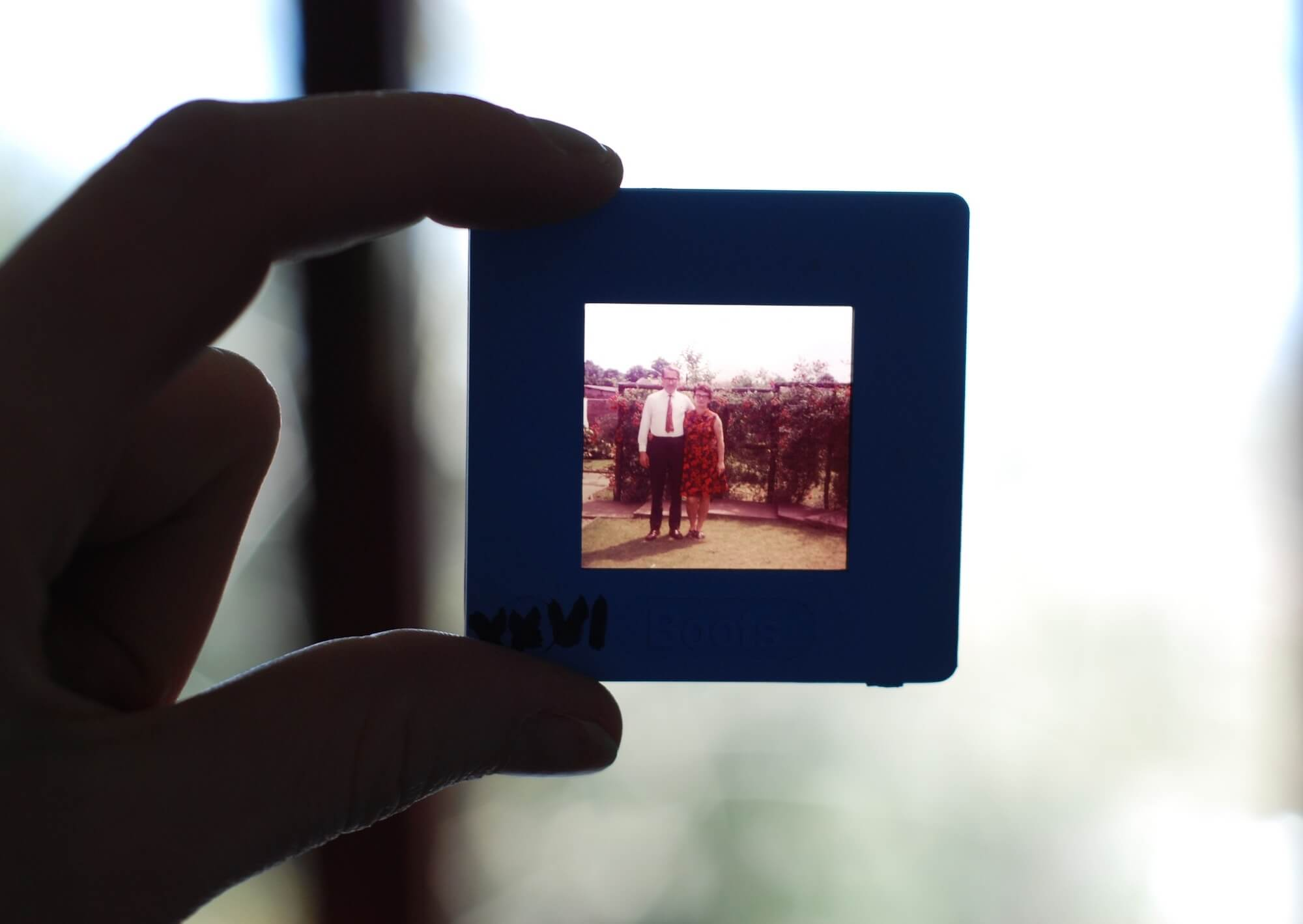 Hand holding projector slide containing an older couple